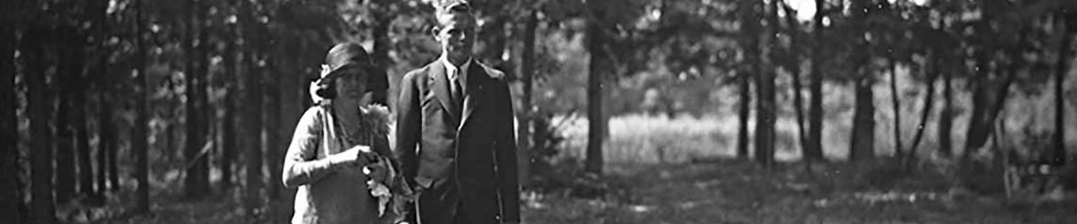 Charles Lindbergh walks next to Anne near some woods.