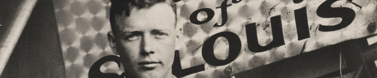 Lindbergh standing in front of a sign, which says Spirit of St. Louis.