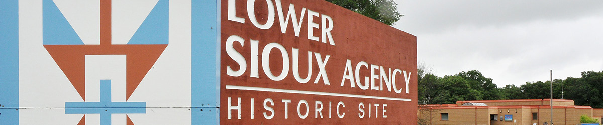 A close-up of a sign: Lower Sioux Agency Historic Site, with the visitor center building in the background.