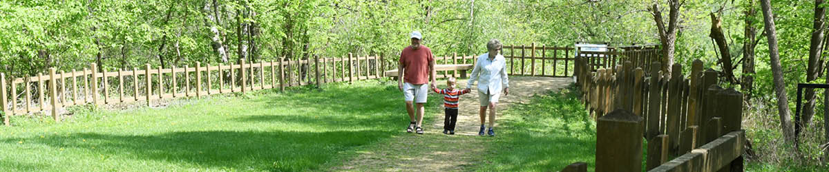 Two adult holding a child's hand on either side, walking in a fenced area.