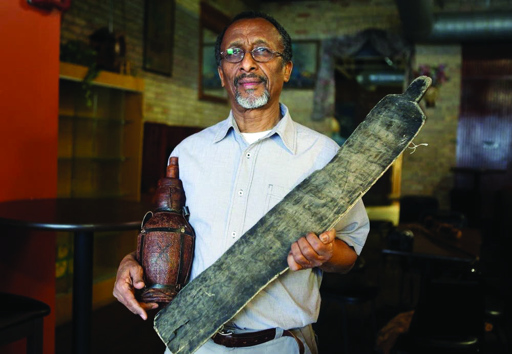 Osman Ali holding artifacts inside the Somali Museum of Minnesota