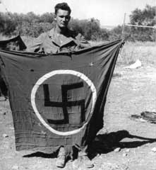 Donald S. Frederick displays a captured Nazi flag in Sicily, 1943.