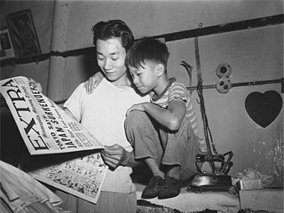 Man and boy reading about Japan's surrender, VJ Day, 1945. Loc. no. E448.17 r11