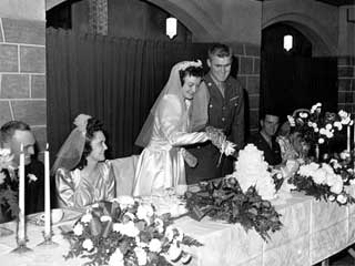 Wedding in the family of Mr. and Mrs. H. Lovas; bride and groom cutting cake, groom in uniform, 1944. Loc. no. Collection I.366.198