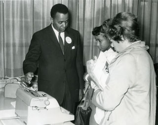 John L. Brown, Sr. demonstrates a typewriter for two prospective customers.