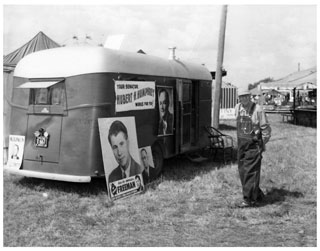 Photo: Trailer posted with campaign signs for Orville Freeman and Hubert H. Humphrey; a small sign for Val Bjornson is on the rear bumper, 1954.