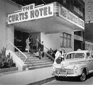 Photo: Guests leaving Curtis Hotel with bellhop, Minneapolis, 1948.