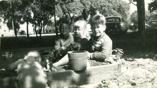 The Day children, playing with a friend in their sandbox, ca. 1949.
