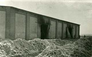 Rear of barn at Gardelegen concentration camp with mass graves in the foreground.