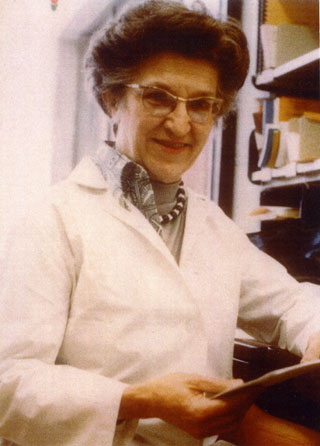 Bee Hanlon, wearing a lab coat, in her office at the University of Minnesota, ca. 1970s.