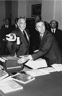 Carl A. Kuhrmeyer demonstrates the 3M overhead projector for Prince Ranier of Monaco.
