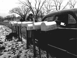 Mail carrier in an automobile placing mail in a row of mailboxes, 1945.