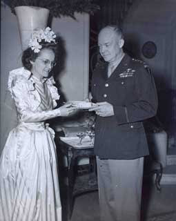 Pearlie Hargrave McKeogh offers General Eisenhower some wedding cake at the reception hosted by the General.