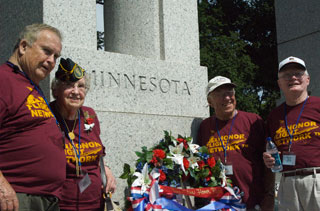 Photo: Minnesota's WWII veterans pose in front of the Minnesota Pillar at the World War II Memorial.