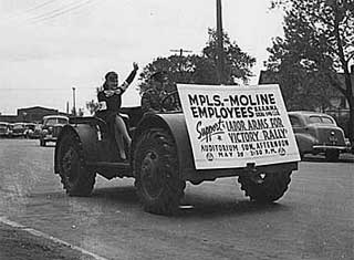 "Minneapolis Moline turns out first ""jeep"", displaying sign for war rally, 1943."