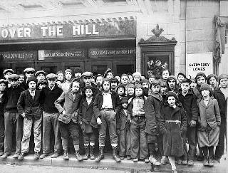 Children standing outside a theater, 1930.