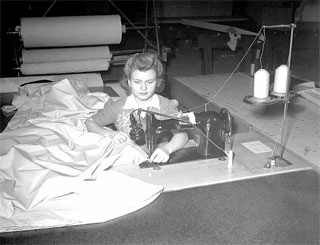 Photo: Seamstress at machine, Northwest Aeronautical Corporation plant, Holman Field, St. Paul, ca. 1942.