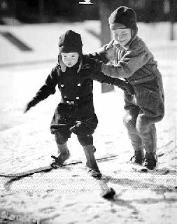 Photo: Young boy helping another young boy manipulate his skis, 1932.