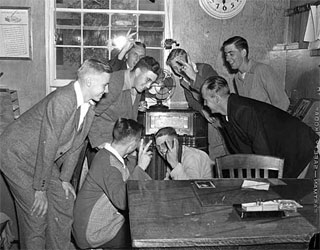 Group gathered around office radio, VJ Day, 1945.