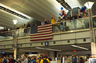 Photo: An enthusiastic crowd welcomed the World War II veterans home from their trip at Minneapolis/St. Paul International Airport.