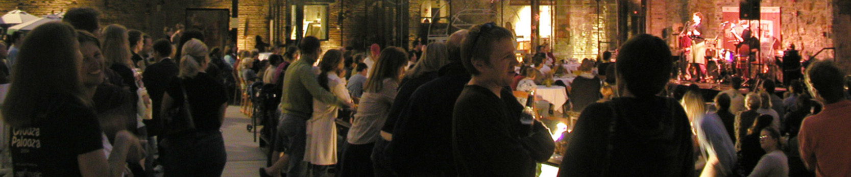 Large crowd of people watching a band play in the ruin courtyard at night.