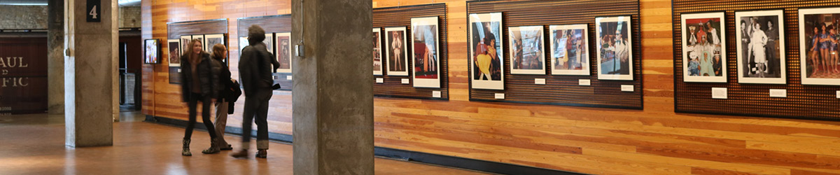 Far view of visitors browsing a wall with photographs hanging in a gallery style.