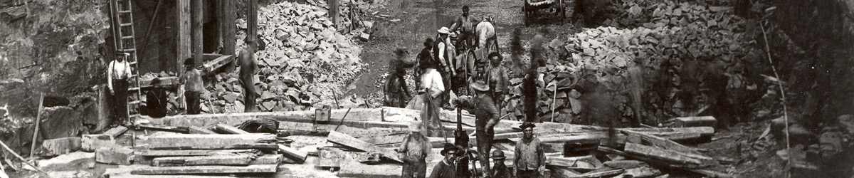 A black and white photo of workers cutting up lumber.