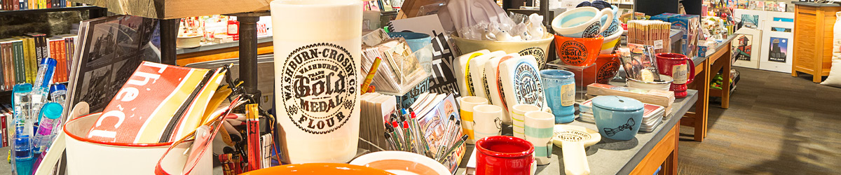 A selection of items sold in the Mill City Museum gift shop: books, mugs, ceramics, and pens.