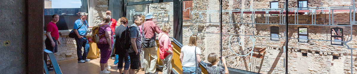 A group of visitors look out over the ruin courtyard from inside the museum.