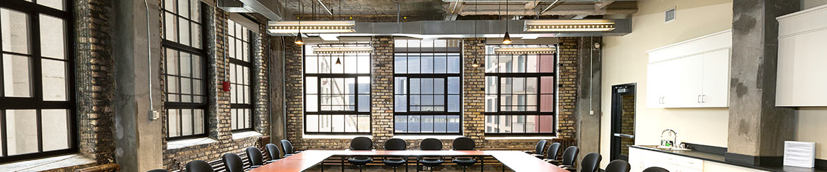 Conference room with exposed stone walls and u shaped table.