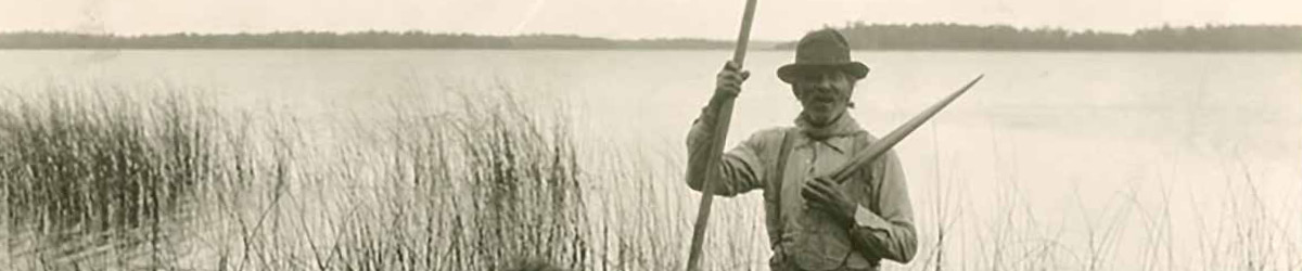 A man in a hat holding a boat paddle standing near a lake with wild rice growing.