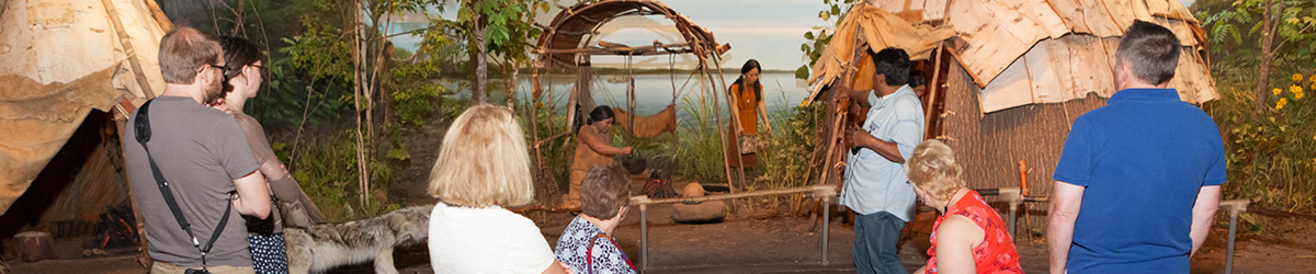 An interpreter is explaining to the audience the Mille Lacs exhibit of Ojibwe life.
