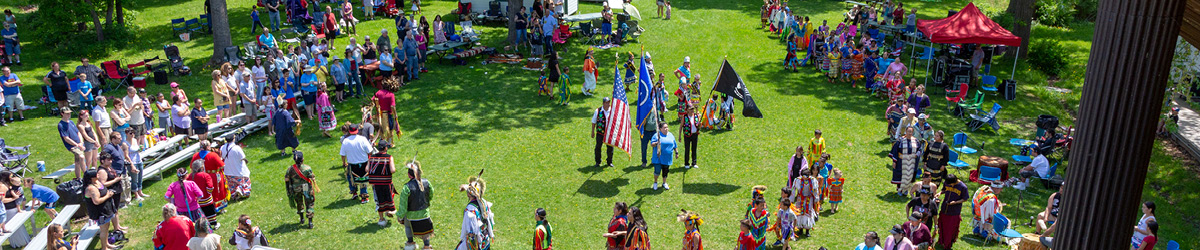 Top view of an outside event with people dressed in traditional Ojibwe costumes.