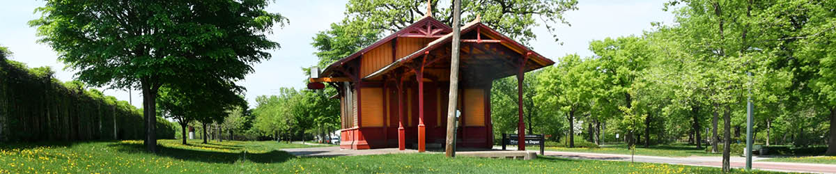 Exterior side view of the Minnehaha Depot surrounded by green trees.