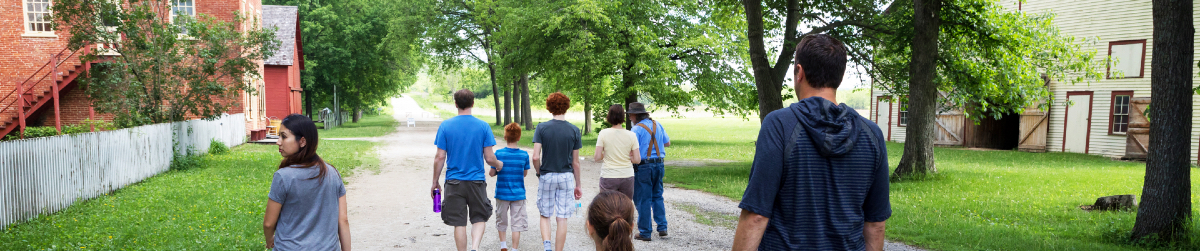A group of people walking down a path at Historic Forestville.