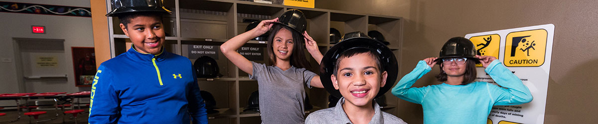 Four kids wearing helmets in the Then Now Wow exhibit.