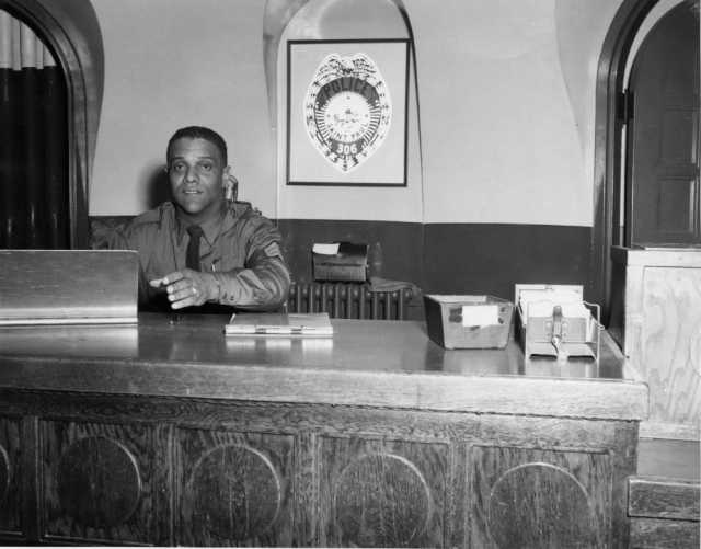 Saint Paul Police Deputy James S. Griffin sitting at his desk, 1960s.