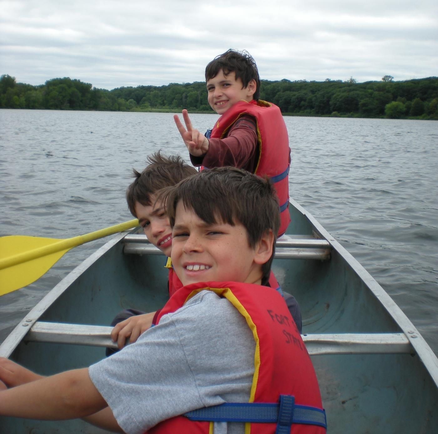 Three boys in a canoe.