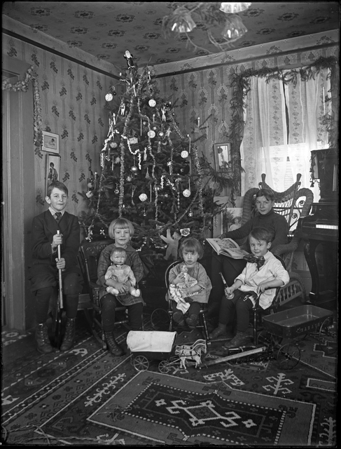 A woman and four children sitting in front of a decorated Christmas tree in a living room