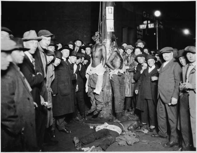 White people making up a lynch mob pose for a photograph after murdering three African American men in Duluth on June 15, 1920