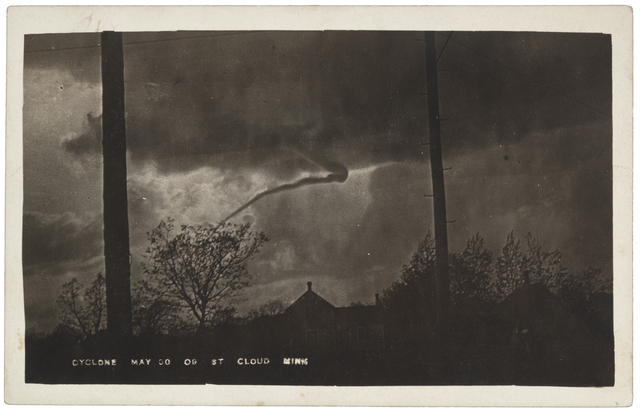 Black-and-white photograph of a cyclone descending from a cloud, above trees and a building