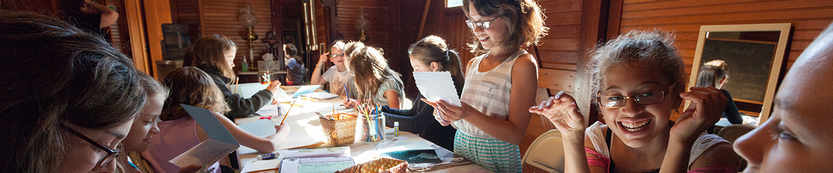 Girls sitting around a table working on a craft