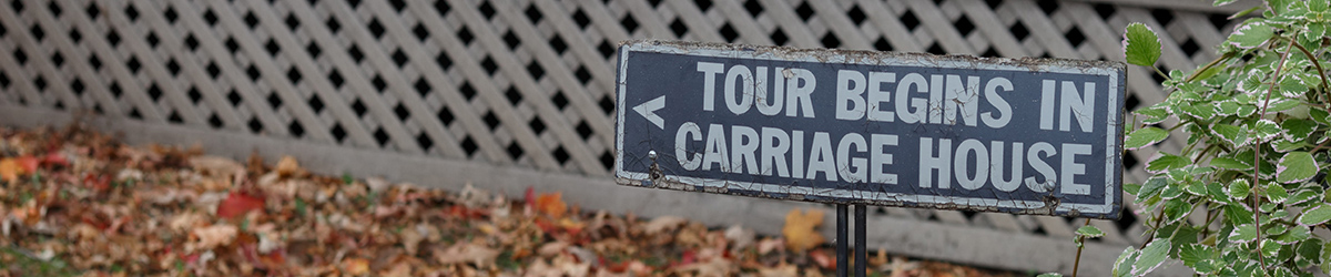 Sign outdoors stating that the tour begins in carriage house
