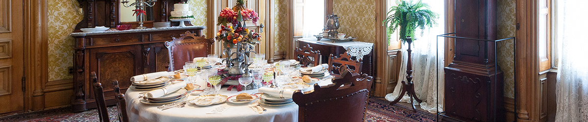 Six settings of antique dishes on dining table with flower centerpiece