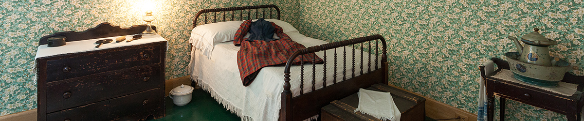 Servants' room with antique bed, dresser, and mirror
