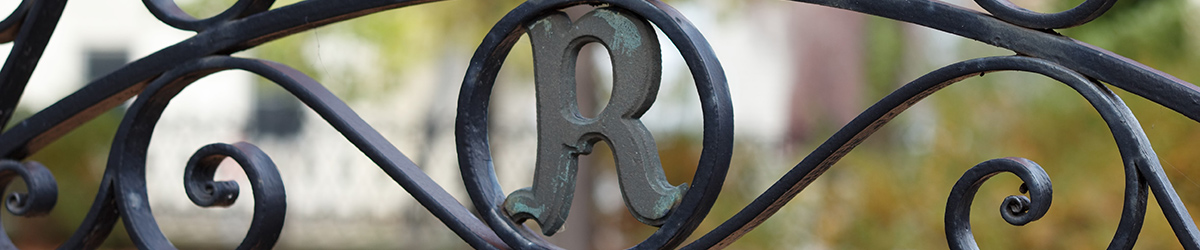 Closeup of iron gate with the letter R