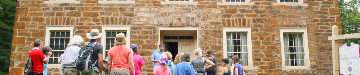 A tour group standing in front of the Sibley house.
