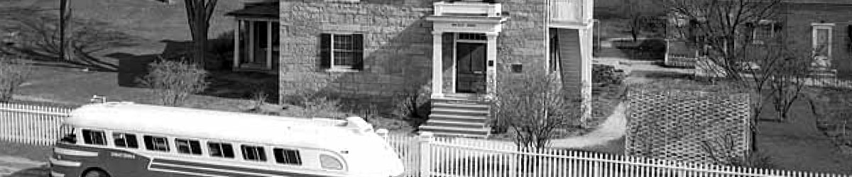 A black and white photo of a bus in front of the Sibley house.