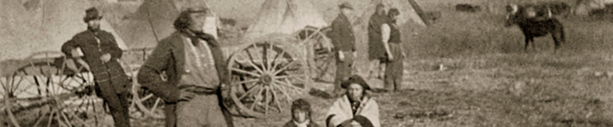 Two people kneeling while several people standing with many tipi in the background.