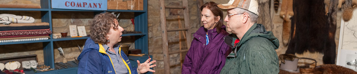 A guide converses with two visitors in the Cold Store at the Sibley Historic Site.
